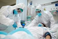 Two healthcare workers wearing full protective gear care for an intubated patient in the ICU who is suffering from COVID.