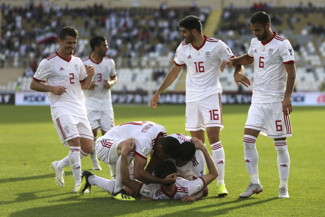 Iran's forward Sardar Azmoun, center bottom, celebrates with his teammates scoring his side's second goal during the AFC Asian Cup group D soccer match between Iran and Vietnam at Al Nahyan Stadium in Abu Dhabi, United Arab Emirates, Saturday, Jan. 12, 2019. (AP Photo/Kamran Jebreili)