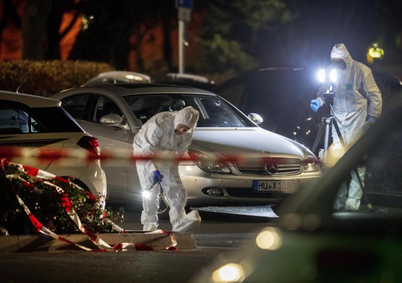Forensics investigate the scene after a shooting in central Hanau, Germany Thursday, Feb. 20, 2020. Eight people were killed in shootings in the German city of Hanau on Wednesday evening, authorities said.  (AP Photo/Michael Probst)