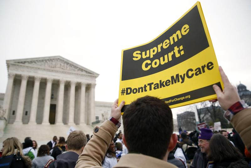 A demonstrator in favor of the Affordable Care Act walks with a sign in front of the Supreme Court in Washington
