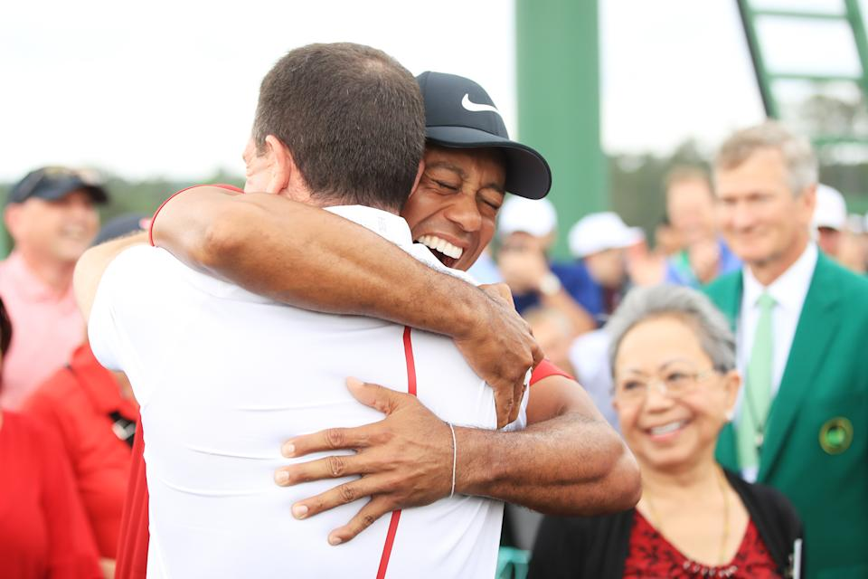 Tiger Woods of the United States embraces his manager Mark Steinberg as he comes off the 18th hole in celebration of his win during the final round of the Masters at Augusta National Golf Club on April 14, 2019 in Augusta, Georgia. (Photo by Andrew Redington/Getty Images)