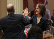 FILE - Sen. Nancy Skinner, D-Berkeley, and Sen. Steven Glazer, D-Orinda slap palms in celebration after her measure to let athletes at California colleges hire agents and sign endorsement deals was approved by the Senate in Sacramento, Calif., in this Wednesday, Sept. 11, 2019, file photo. The NCAA Board of Directors is expected to greenlight one of the biggest changes in the history of college athletics when it clears the way for athletes to start earning money based on their fame and celebrity without fear of endangering their eligibility or putting their school in jeopardy of violating amateurism rules that have stood for decades.(AP Photo/Rich Pedroncelli, File)