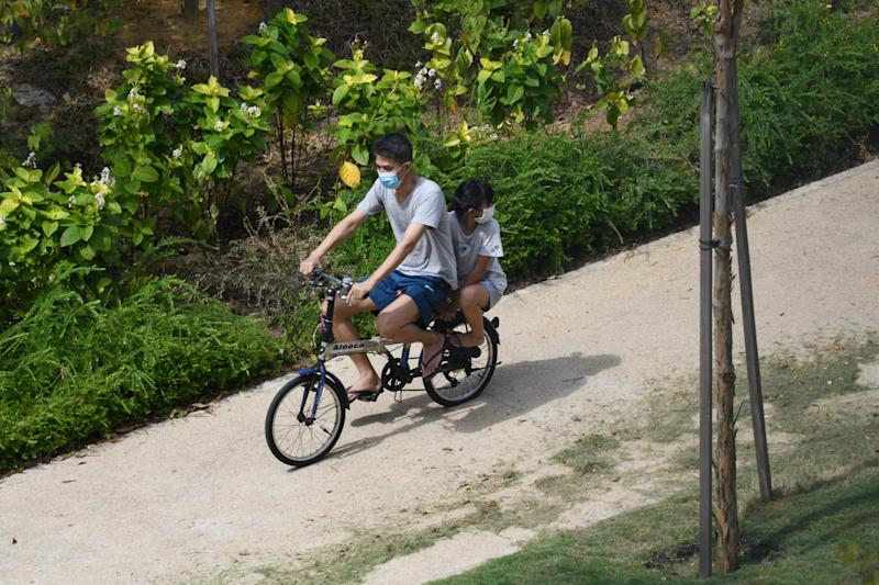 A man cycles with his daughter along a neighbourhood housing estate in Singapore on August 10, 2020. (Photo by Roslan RAHMAN / AFP) (Photo by ROSLAN RAHMAN/AFP via Getty Images)