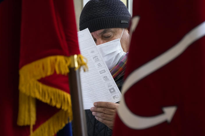 A man examines his ballot during the State Duma, the Lower House of the Russian Parliament and local parliaments elections at a polling station in St. Petersburg, Russia, Saturday, Sept. 18, 2021. Sunday will be the last of three days voting for a new parliament, but there seems to be no expectation that United Russia, the party devoted to President Vladimir Putin, will lose its dominance in the State Duma. (AP Photo/Dmitri Lovetsky)