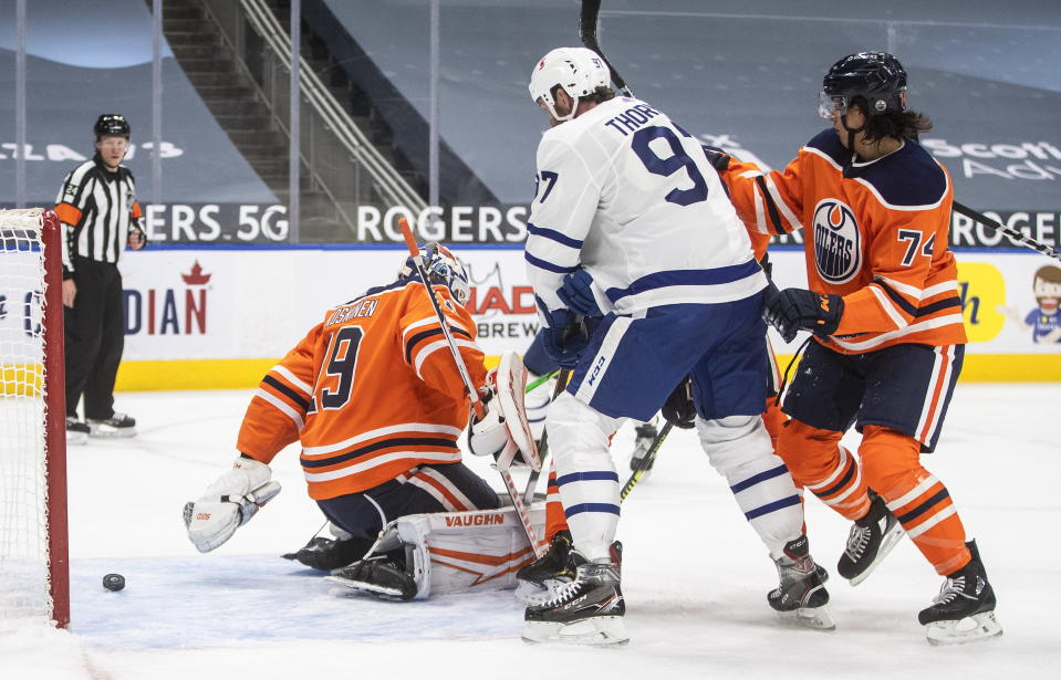 Edmonton Oilers goalie Mikko Koskinen (19) is scored on as Toronto Maple Leafs Joe Thornton (97) and Ethan Bear (74) battle in front during first-period NHL hockey game action in Edmonton, Alberta, Monday, March 1, 2021. (Jason Franson/The Canadian Press via AP)