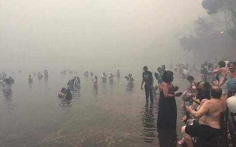Dozens of people flee to the beach in Mati - Credit: Blitz Pictures