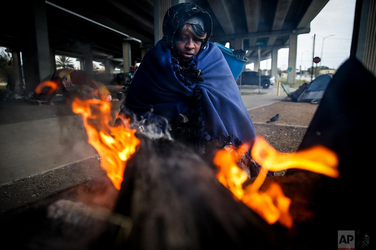 <p>Tony Sampson, who received a blanket from Star of Hope's Love in Action van, tries to warm up by a fire under the Eastex Freeway as temperatures hover in the 30s in Houston. Plunging overnight temperatures in Texas brought rare snow flurries as far south as Austin, and accidents racked up on icy roads across the state. (Michael Ciaglo/Houston Chronicle via AP) </p>