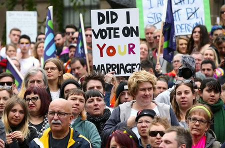 People carry banners and signs as they participate in a marriage equality march in Melbourne Australia