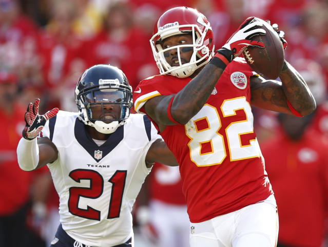 Kansas City Chiefs wide receiver Dwayne Bowe (82) catches a pass while covered by Houston Texans cornerback Brice McCain (21) during the first half of an NFL football game at Arrowhead Stadium in Kansas City, Mo., Sunday, Oct. 20, 2013. (AP Photo/Ed Zurga)