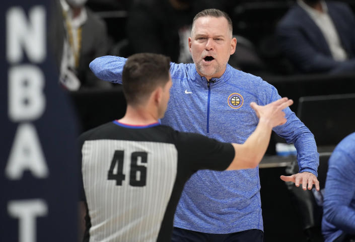 Denver Nuggets coach Michael Malone, back, makes a point to referee Ben Taylor during the second half of Game 3 of the team's NBA second-round playoff series against the Phoenix Suns on Friday, June 11, 2021, in Denver. (AP Photo/David Zalubowski)