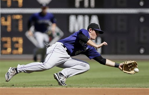 Colorado Rockies second baseman DJ LeMahieu dives for a ground out by Philadelphia Phillies' Nate Schierholtz in the first inning of the first game of a baseball doubleheader, Sunday, Sept. 9, 2012, in Philadelphia. (AP Photo/Matt Slocum)
