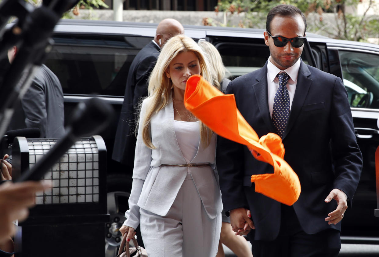 "An orange shirt saying ""inmate"" is thrown by a protester at former Donald Trump presidential campaign foreign policy adviser George Papadopoulos, right. (Photo: Jacquelyn Martin/AP)"