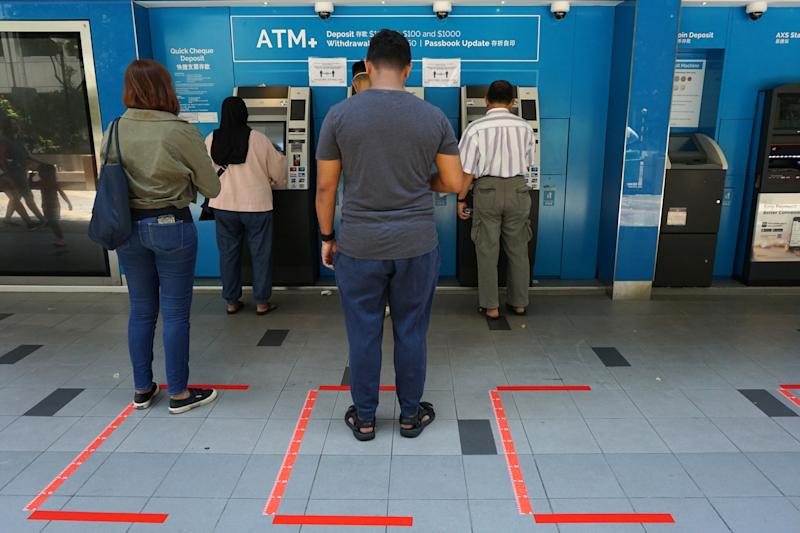 People wait to use ATM machines while standing in areas demarcated for social distancing, as a preventive measure against the spread of the COVID-19 novel coronavirus, at Tanjong Pagar Plaza in Singapore on April 1, 2020. (Photo by Roslan RAHMAN / AFP) (Photo by ROSLAN RAHMAN/AFP via Getty Images)