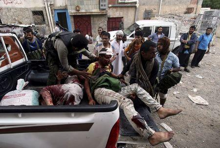 Fighters of the Popular Resistance Committees rush comrades to a hospital after they were injured during clashes with Houthi fighters in Yemen's southwestern city of Taiz