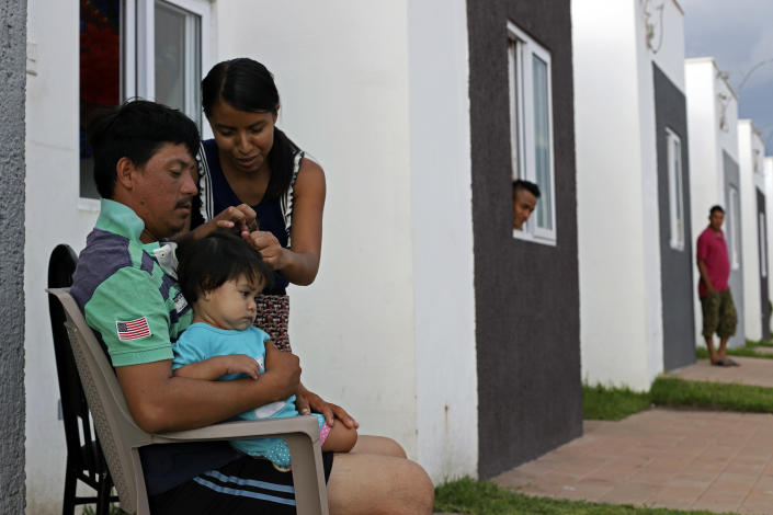 Elmer Erroa holds his daughter Ruth as his wife Lorena combs her hair, on the doorstep of their new government donated home, in the private development Ciudad Marsella, El Salvador, Tuesday, July 27, 2021. The Erroas, who were displaced by the October 2020 landslide triggered by a tropical storm, are among the families who were given a government-issued check in December for $25,300 to purchase the home in the middle-class community. (AP Photo/Salvador Melendez)