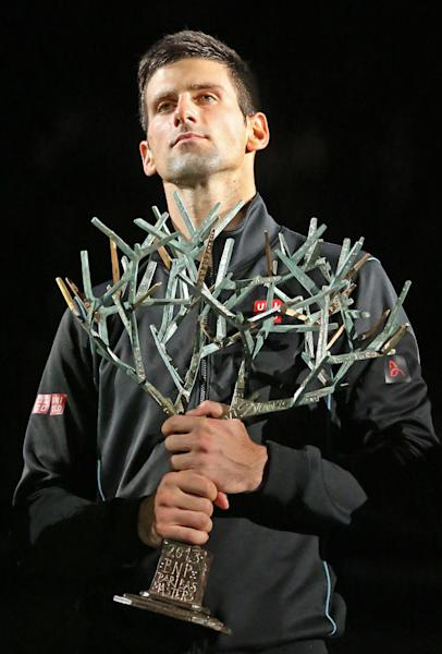 Serbia's Novak Djokovic holds the trophy after winning the final of the Paris Masters tennis against Spain's David Ferrer, in the Paris Bercy stadium, Sunday Nov. 3, 2013.(AP Photo/Remy de la Mauviniere)