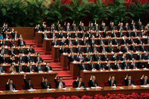 Chinese leaders raise their hands to vote during the closing session of the 17th Communist Party Congress at the Great Hall of the People in Beijing in 2007. China's top communist party newspaper said Sunday that preparations for a key meeting to set the country's next leadership were smooth, despite a festering political scandal