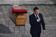 French President Emmanuel Macron leaves after paying his respects by the coffin of slain teacher Samuel Paty in the courtyard of the Sorbonne university during a national memorial event, Wednesday, Oct. 21, 2020 in Paris. French history teacher Samuel Paty was beheaded in Conflans-Sainte-Honorine, northwest of Paris, by a 18-year-old Moscow-born Chechen refugee, who was later shot dead by police. (AP Photo/Francois Mori, Pool)