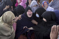 Women from the Shiite Hazara community mourn over death of their family members during at a sit-in protest against the killing of coal mine workers by unknown gunmen near the Machh coal field, in Quetta, Pakistan, Monday, Jan. 4, 2021. Gunmen opened fire on a group of minority Shiite Hazara coal miners after abducting them, killing 11 in southwestern Baluchistan province early Sunday, a Pakistani official said. (AP Photo/Arshad Butt)