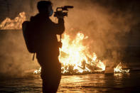 A cameraman films fire after clashes broke out during a protest against the government restriction measures to curb the spread of COVID-19 in Turin, Italy, Monday, Oct. 26, 2020. Protesters turned out by the hundreds in Italian several cities and towns on Monday to vent anger, sometimes violently, over the latest anti-COVID-19 rules, which force restaurants and cafes to close early, shutter cinema, gyms and other leisure venues. In the northern city of Turin, demonstrators broke off from a peaceful protest and hurled smoke bombs and bottles at police in the city square where the Piedmont regional government is headquartered. (Claudio Furlan/LaPresse via AP)