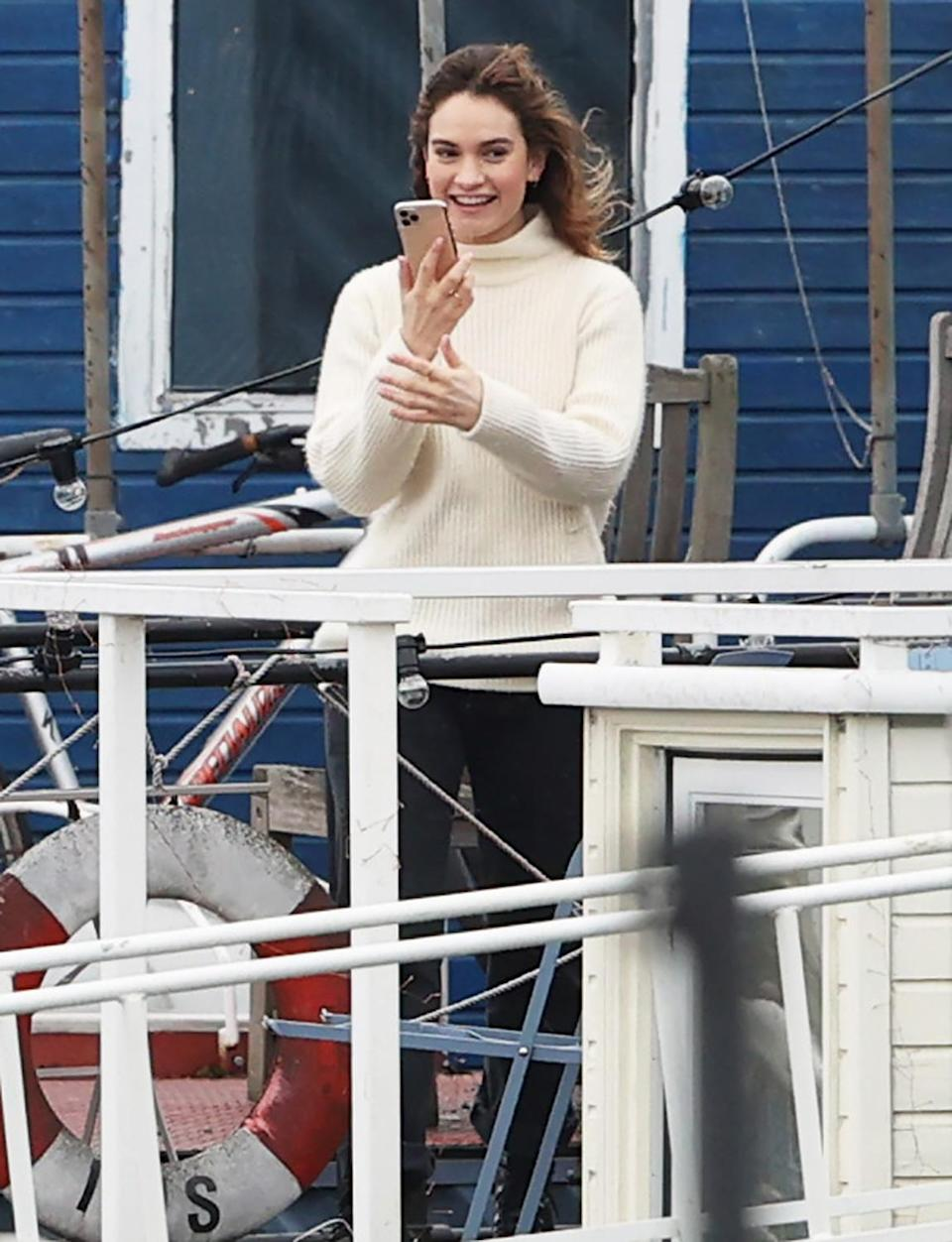 <p>Lily James is seen on the set of <em>What's Love Got to Do with It,</em> as she tries to set a Tinder date on her phone, on Friday in London. </p>