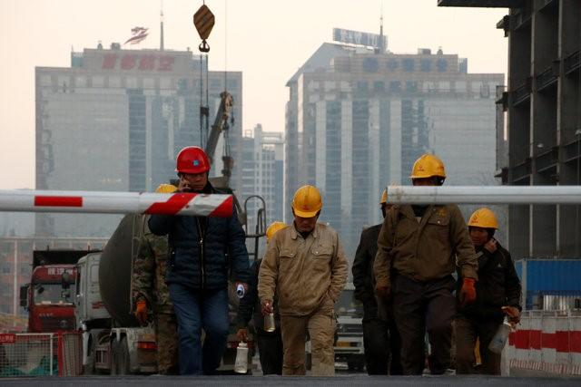 Workers leave a construction site at the end of their shift in Beijing