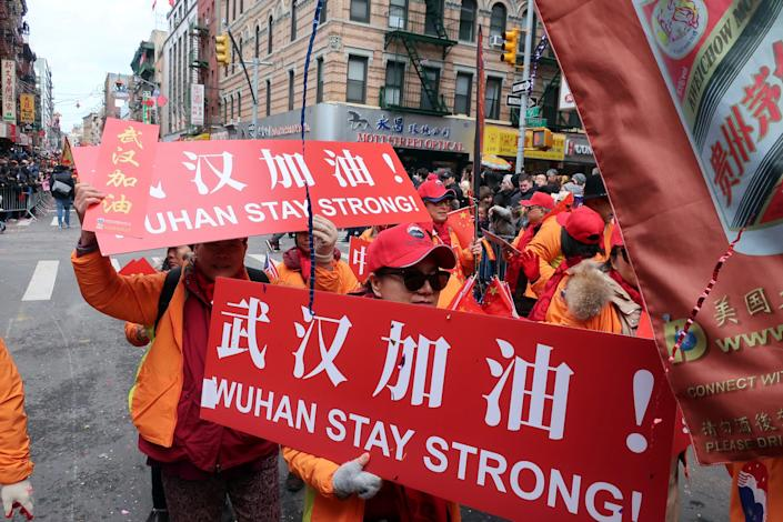 People carry signs in support of Wuhan, China, at the center of the coronavirus outbreak, during the Lunar New Year parade, Sunday, Feb. 9, 2020, in Manhattan's Chinatown, in New York.