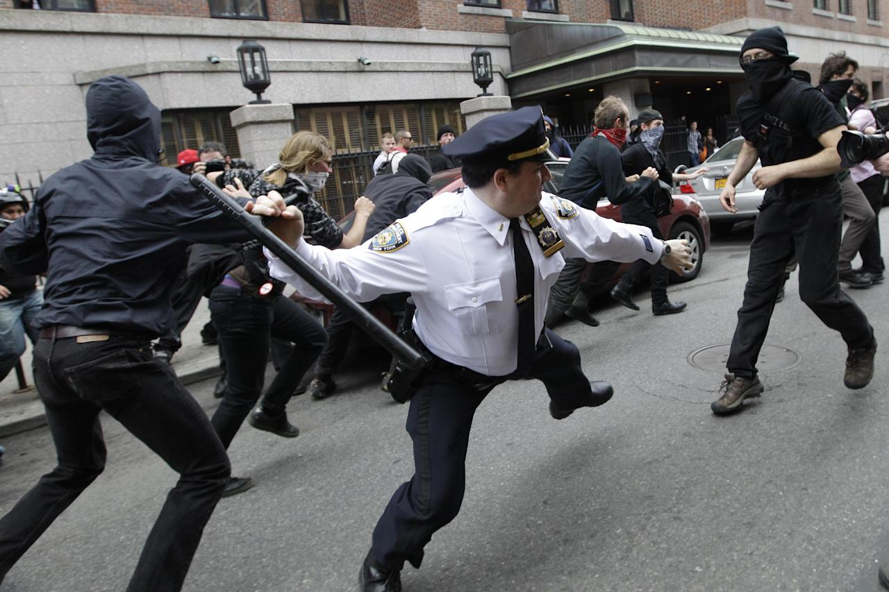 A police lieutenant swings his baton at an Occupy Wall Street activists on Tuesday, May 1, 2012 in New York. Hundreds of activists with a variety of causes spread out over New York City Tuesday on International Workers Day, or May Day, with Occupy Wall Street members leading a charge against financial institutions. (AP Photo/Mary Altaffer)