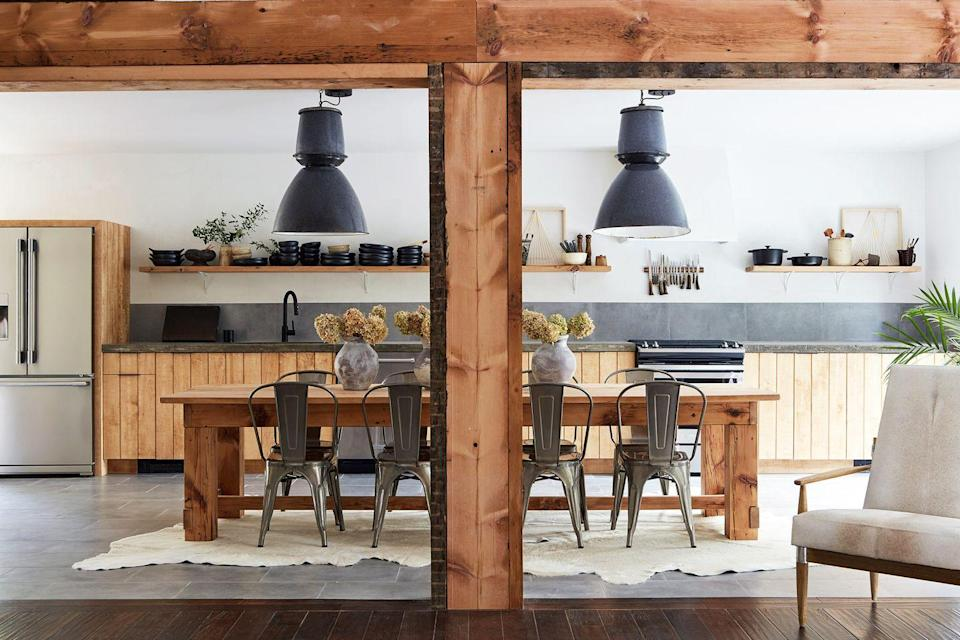 <p>If you're kitchen is blessed with tons of counter room for cooking and you want to try something different with the leftover space, fill it with a dining table instead. Choose something with similar proportions, like a large rustic dining table, to achieve a similar layout but with a new twist. We're also into the hide area rug under the table in this kitchen designed by Leanne Ford—it's a the perfect dose of warmth. </p>