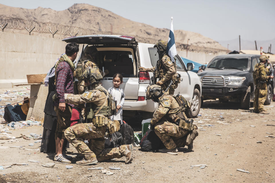In this image provided by the U.S. Marine Corps, Finnish coalition forces assist evacuees for onward processing during an evacuation at Hamid Karzai International Airport in Kabul, Afghanistan, on Tuesday, Aug. 24, 2021. As the U.S. rushes to evacuate Americans and allies from Afghanistan, a growing number of Republicans are questioning why the U.S. should take in Afghan citizens who worked side by side with Americans. (Staff Sgt. Victor Mancilla/U.S. Marine Corps via AP)