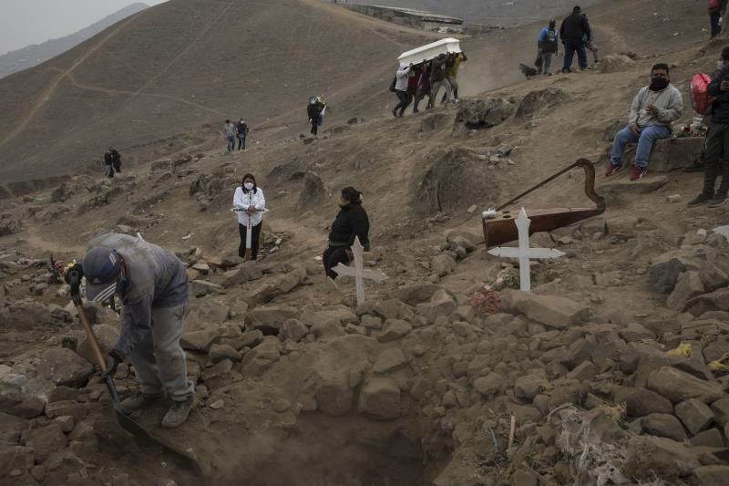 A cemetery worker shovels dirt into the grave of Apolonia Uanampa, who died of the new coronavirus, as the remains of Demetria Huamani, also a virus victim, are carried to a grave site at the Nueva Esperanza cemetery on the outskirts of Lima, Peru, Wednesday, May 27, 2020. (AP Photo/Rodrigo Abd)