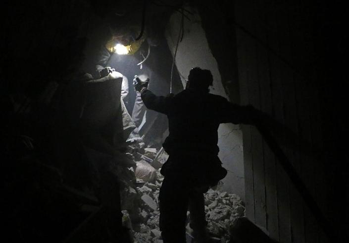Syrian rescuers work in the battered rebel enclave Eastern Ghouta on February 22, 2018 (AFP Photo/Hamza AL-AJWEH)