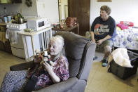Karen Colby listens in on July 22, 2021 while her neighbor Joel Aslin tells how he called an ambulance for her when she got heat stroke as temperatures reached 107 F in her small fifth-floor studio apartment during a record-breaking heat wave in June, in Portland, Ore. The unprecedented heat, which reached 116 F in Portland, killed dozens of people in Oregon and hundreds across the region and was a wake-up call for the normally cool region as climate change accelerates. (AP Photo/Gillian Flaccus)