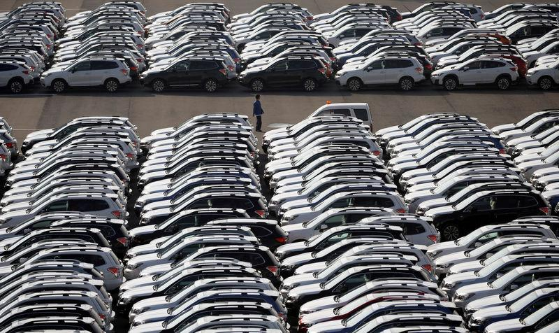 A worker is seen among newly manufactured cars awaiting export at the port in Yokohama
