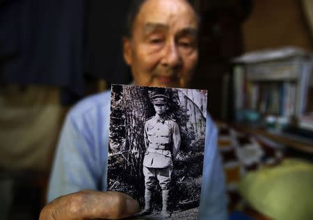 Inokuma, a former Imperial Japanese Army soldier, shows a photograph of him taken in 1944, during an interview with Reuters at his home in Yokosuka
