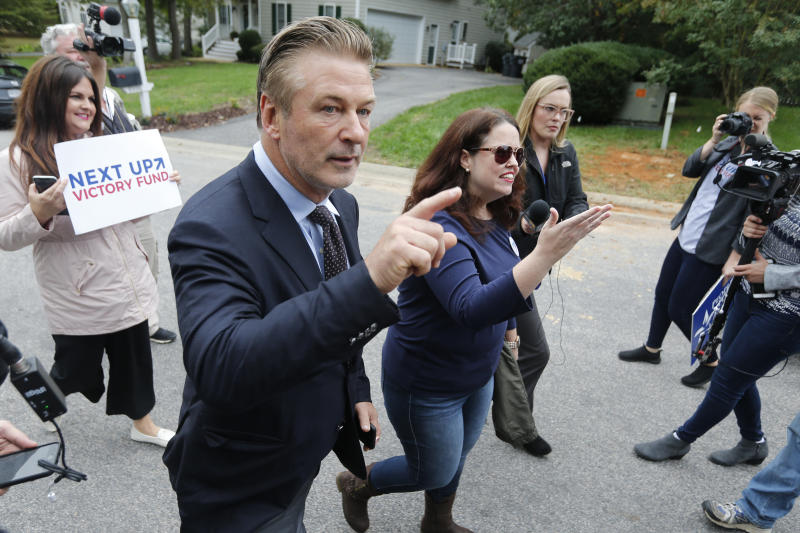 Actor Alec Baldwin, left, walks with Amanda Pohl, candidate for Virginia Senate District 11 in her neighborhood in Midlothian, Va., Tuesday, Oct. 22, 2019. Baldwin campaigned for several candidates around the state. (AP Photo/Steve Helber)