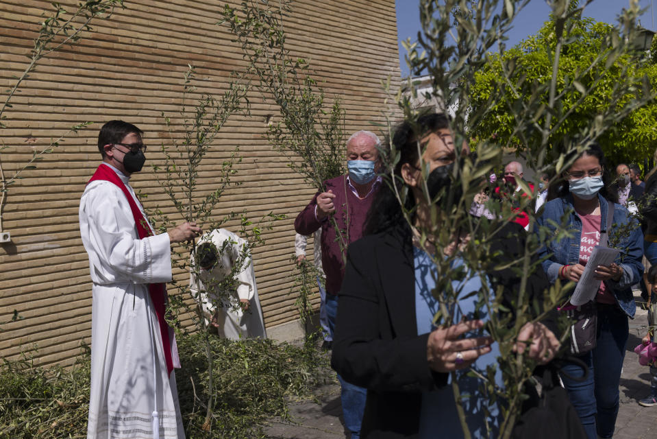 A Catholic priest distributes palms among worshipers prior to a Palm Sunday mass during the Holy Week, outside Nuestra Senora de la Candelaria church in Seville, southern Spain, Sunday, March 28, 2021. Few Catholics in devout southern Spain would have imagined an April without the pomp and ceremony of Holy Week processions. With the coronavirus pandemic unremitting, they will miss them for a second year. (AP Photo/Laura Leon)