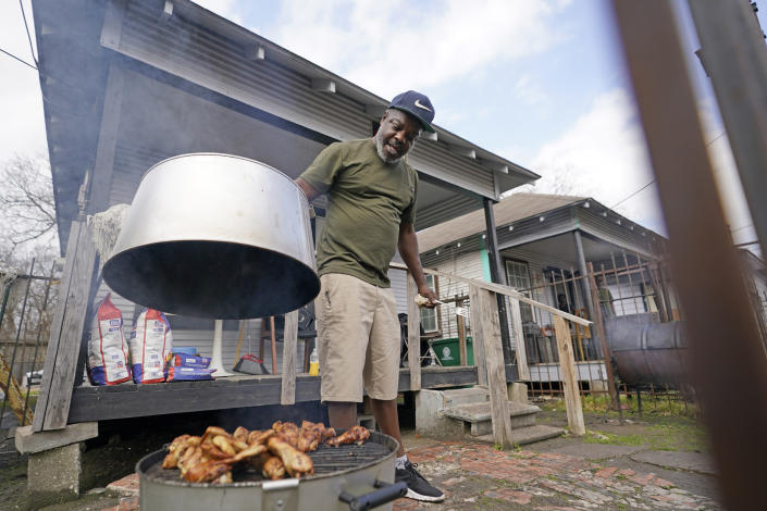 Thomas Watkins barbecues outside his home, which was without running water for days after a recent winter storm, Friday, Feb. 26, 2021, in Houston. Local officials, including Houston Mayor Sylvester Turner, say they have focused their efforts during the different disasters on helping the underserved and under-resourced but that their work is far from complete. (AP Photo/David J. Phillip)