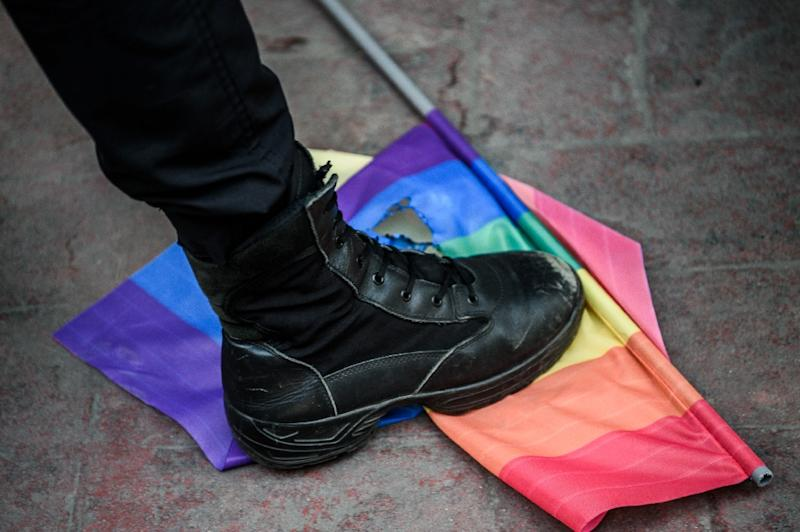 A Turkish anti-riot police officer steps on a rainbow flag during a rally staged by the LGBT community on Istiklal avenue in Istanbul on June 19, 2016 (AFP Photo/Ozan Kose)