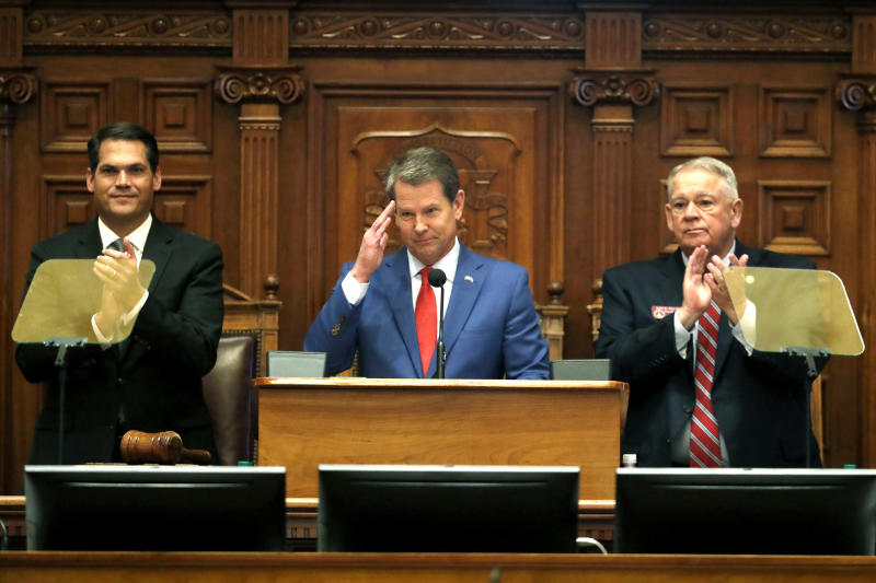 FILE - In this Jan. 16, 2020, file photo, Gov. Brian Kemp, center, is flanked by House Speaker David Ralston, R-Blue Ridge, right, and Lt. Gov. Geoff Duncan as he salutes former U.S. Senator Johnny Isakson, R-Ga., during the State of the State address before a joint session of the Georgia General Assembly in Atlanta. House Bill 757 passed Monday, Jan. 27, out of a House subcommittee. GOP Gov. Brian Kemp has threatened a veto. (AP Photo/John Bazemore, File)