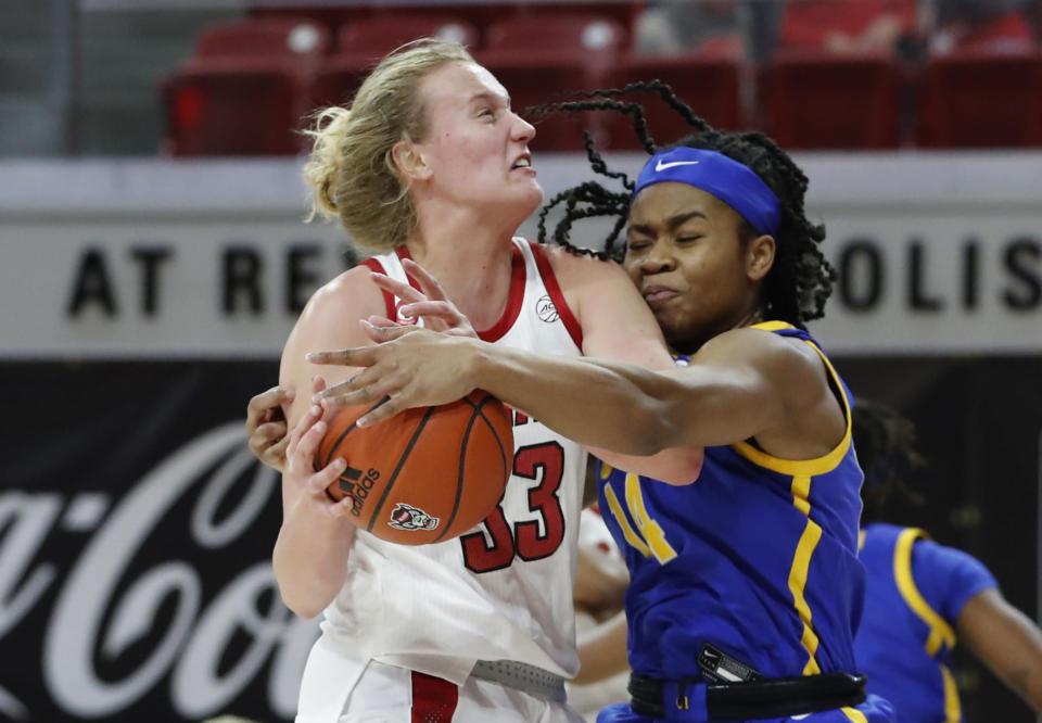 Pittsburgh's Cynthia Ezeja (14) knocks the ball from the hands of North Carolina State's Elissa Cunane (33) during the first half of an NCAA college basketball game, Thursday, Feb. 25, 2021 in Raleigh, N.C. (Ethan Hyman/The News & Observer via AP, Pool)
