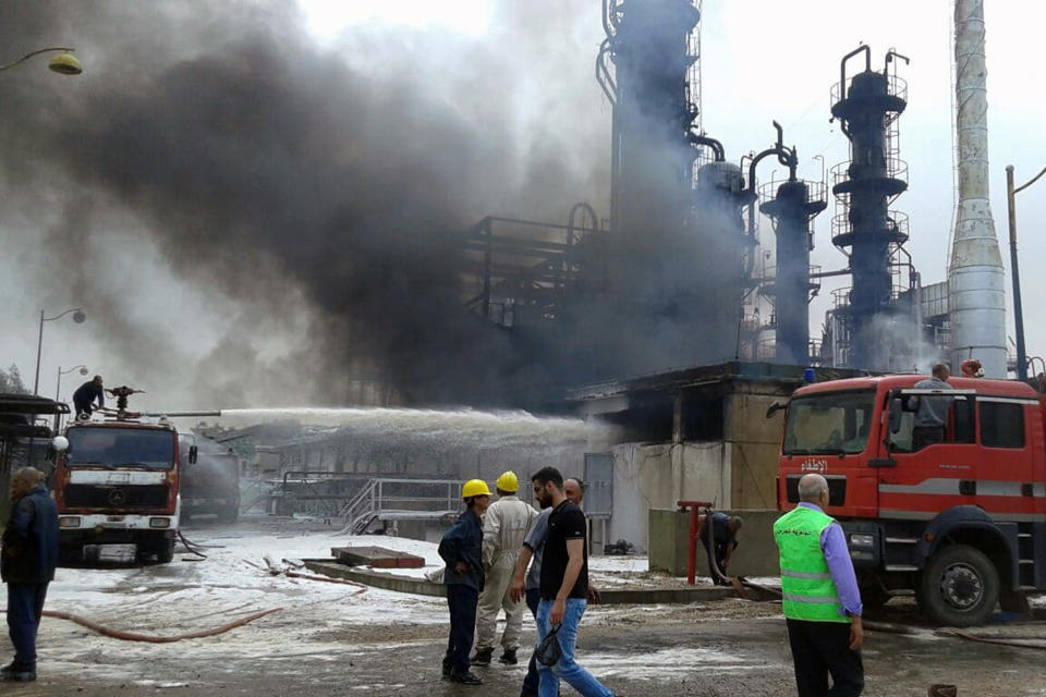 In this photo released by the Syrian official news agency SANA, firefighters put out a fire at the Homs Oil Refinery in the central province of Homs, Syria, Sunday, May. 9, 2021. The fire came amid a series of mysterious attacks on vessels and oil facilities in Syria over the past months. The war-torn country has been suffering from fuel shortages in recent months. (SANA via AP)