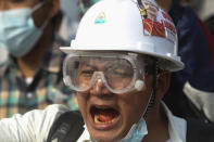 A protester wears a safety helmet and eye protector as he shouts slogans during a protest against the military coup in Yangon, Myanmar, Sunday, Feb. 28, 2021. Police fired tear gas and water cannons and there were reports of gunfire Sunday in Myanmar's largest city Yangon where another anti-coup protest was underway with scores of students and other demonstrators hauled away in police trucks. (AP Photo)