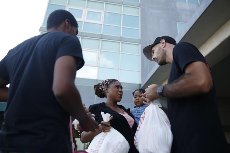 "Volunteer Nick Mills, right, hands Hurricane Dorian evacuee, Leshonda Collins and her 1-year-old daughter Shayniyah, supplies as they arrive from the Grand Celebration cruise ship from Freeport, a city in the Grand Bahamas on Wednesday, Sept. 18, 2019 in Riviera Beach. The cruise ship transported hundreds of evacuees seeking passage from Freeport after the damaged caused by Hurricane Dorian. ""I'm happy to be in the U.S., I'm going to work, work, work, and try to get a job,"" says Collins. (AP Photo/Brynn Anderson)"