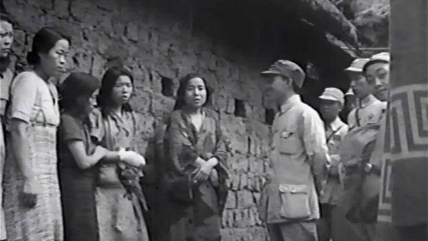 Seven 'comfort women' are seen standing next to a Chinese soldier during World War II. Source: US National Archives