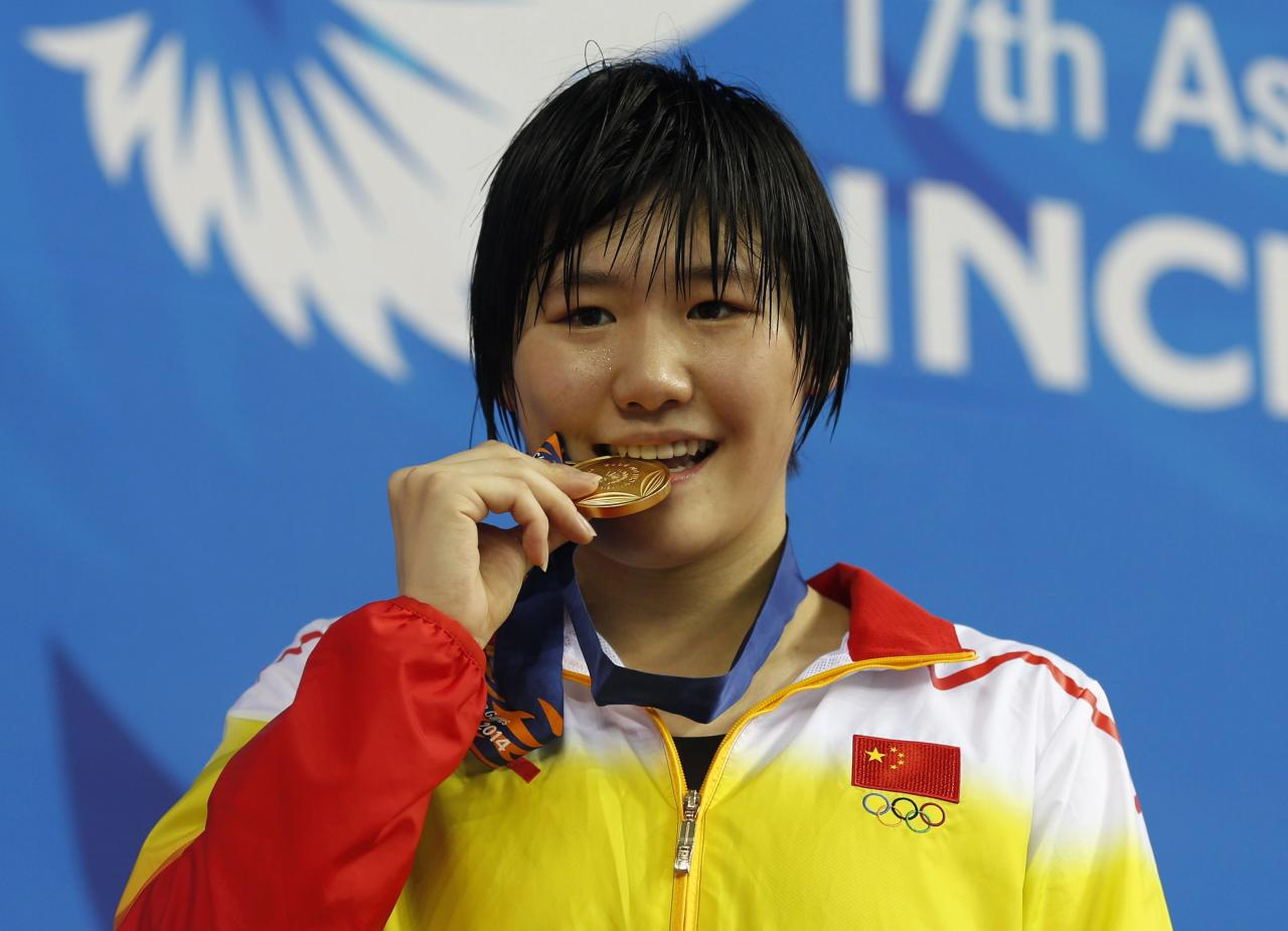 China's Ye Shiwen bites her gold medal after winning the women's 200m individual medley final swimming competition at the Munhak Park Tae-hwan Aquatics Center during the 17th Asian Games in Incheon September 26, 2014. REUTERS/Tim Wimborne (SOUTH KOREA - Tags: SPORT SWIMMING)