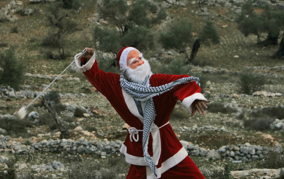 <p>A Palestinian demonstrator dressed as Santa Claus uses a sling-shot to hurl stones at Israeli border police during a demonstration against Israel's separation barrier in the West Bank village of Bilin near Ramallah, Dec. 26, 2008. Israel says the barrier is necessary for security while Palestinians call it a land grab. (Photo: Muhammed Muheisen/AP) </p>