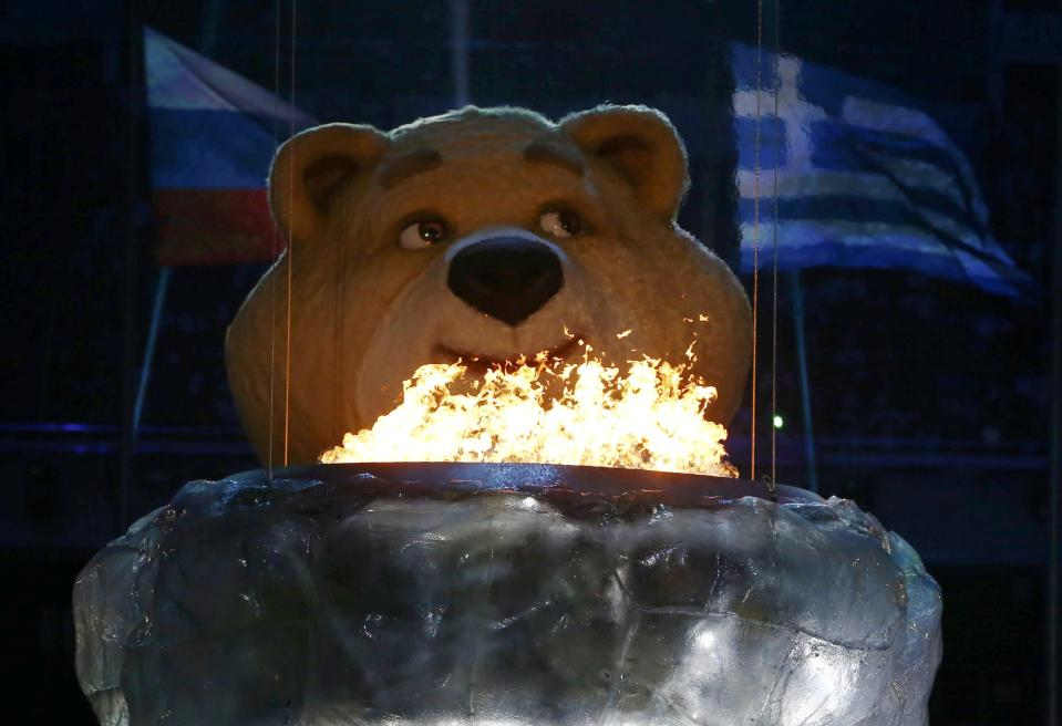 An Olympic Games mascot pauses before extinguishing the Olympic flame in a small cauldron in the stadium during the closing ceremony for the Sochi 2014 Winter Olympics, February 23, 2014. REUTERS/Marko Djurica (RUSSIA - Tags: SPORT OLYMPICS)