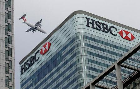 An aircraft flies past the HSBC headquarters building in the Canary Wharf financial district in east London