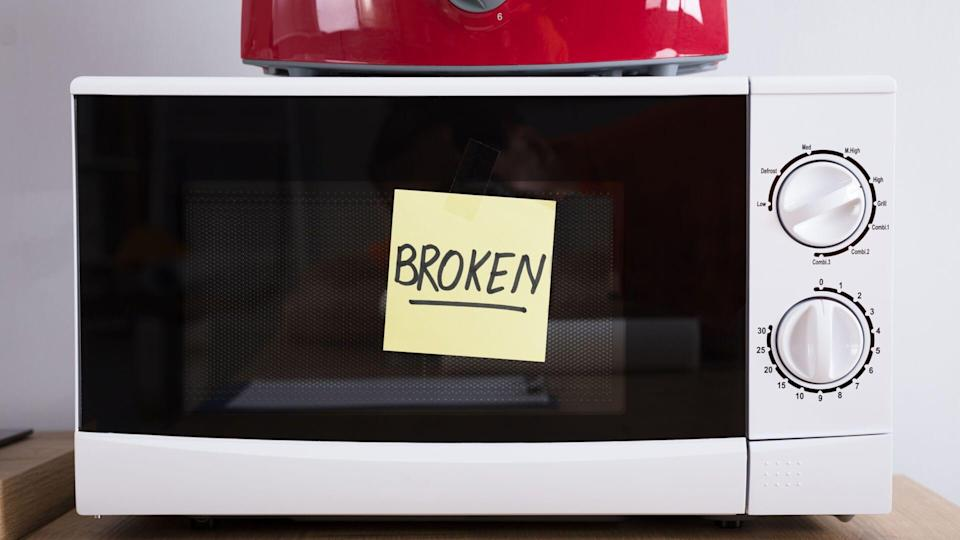 Close-up Of A Microwave Oven With Adhesive Notes Showing Broken Text.